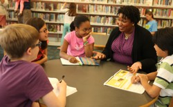 Stacey Abrams speaks with a group of children