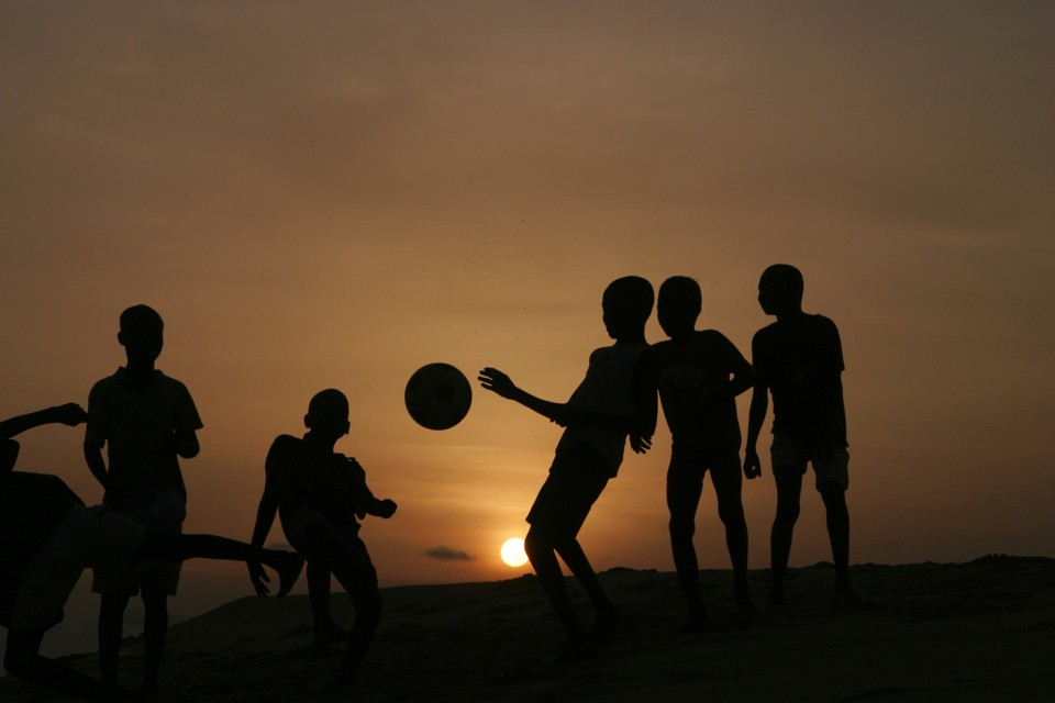 The silhouettes of a group of children kicking a soccer ball in front of the setting sun