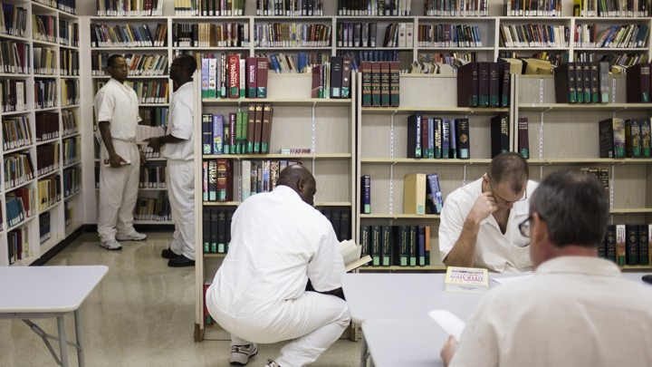 Men dressed in all white sit in a fluorescent room with bookshelves