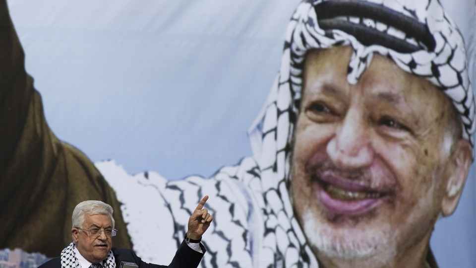 Palestinian President Mahmoud Abbas gestures beneath a poster of the late Palestinian leader Yasser Arafat, during a rally marking the anniversary of Arafat's death in Ramallah on November 11, 2014.