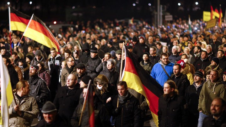 "Participants hold German national flags during a demonstration called by anti-immigration group Pegida, a German abbreviation for ""Patriotic Europeans against the Islamization of the West"", in Dresden on December 15, 2014."