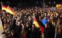 """Participants hold German national flags during a demonstration called by anti-immigration group Pegida, a German abbreviation for """"Patriotic Europeans against the Islamization of the West"""", in Dresden on December 15, 2014."""