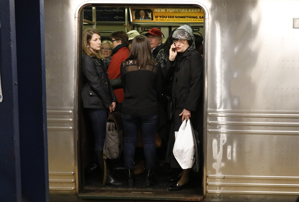Commuters standing in a crowded train car