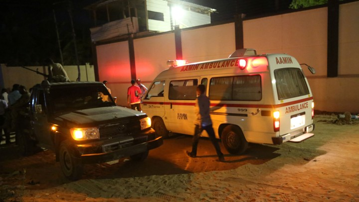 A man walks past an ambulance and armed security forces at the scene of an attackin Mogadishu, Somalia, on June 14, 2017.