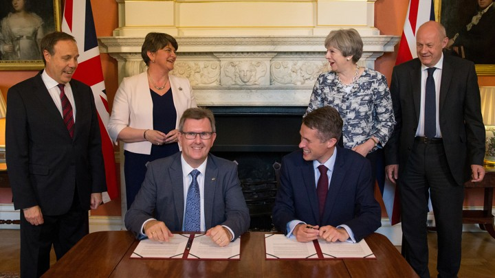 Prime Minister Theresa May stands next to Democratic Unionist Party leader Arlene Foster, as DUP MP Jeffrey Donaldson signs the agreement with Gavin Williamson, Britain's parliamentary secretary to the Treasury and chief whip.