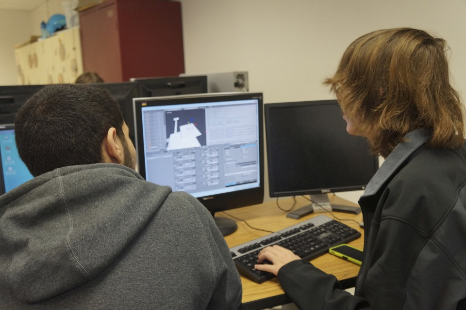 Taken from behind them, two young men stare at a computer screen