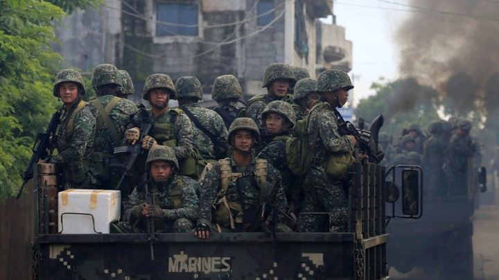 Soldiers onboard military trucks ride along the main street as government troops continue their assault on insurgents from the Maute group, who have taken over large parts of Marawi City, Philippines.