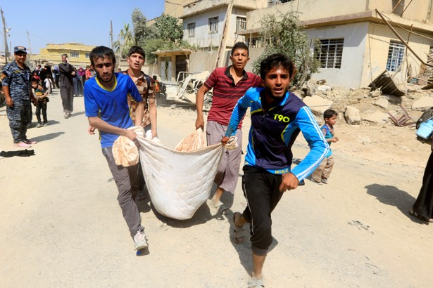 Displaced Iraqi men carry a wounded boy from clashes in western Mosul, Iraq on June 3, 2017.