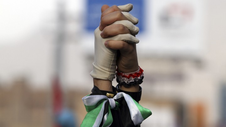 Women clasp hands during a pro-democracy march to demand Yemen's former President Ali Abdullah Saleh stand trial for the killings of protesters who demanded the end of his 33-year rule, in Sanaa on April 8, 2013.