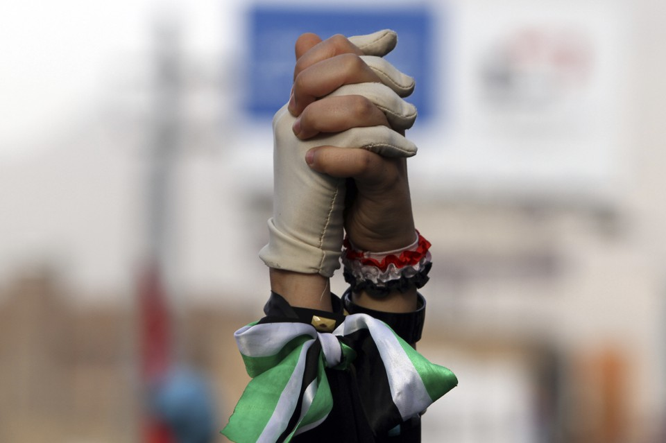 Women clasp hands during a pro-democracy march to demand Yemen's former President Ali Abdullah Saleh stand trial for the killings of protesters who demanded the end of his 33-year rule, in Sanaa April 8, 2013.