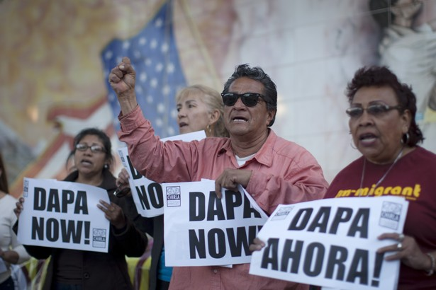 Members of the Coalition for Humane Immigrant Rights of Los Angeles hold signs outside a vigil for immigrants at Our Lady Queen of Angels Church on April 16, 2015.