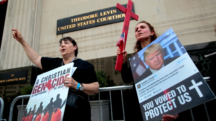 Protesters rally outside the federal court before a hearing to consider a class-action lawsuit filed on behalf of Iraqi nationals facing deportation, in Detroit, Michigan, June 21, 2017.