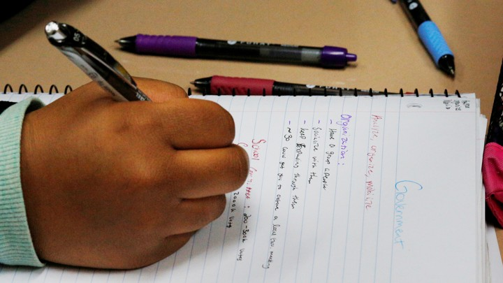 A student holds a pencil above a sheet of notebook paper. The notes appear to be about the government