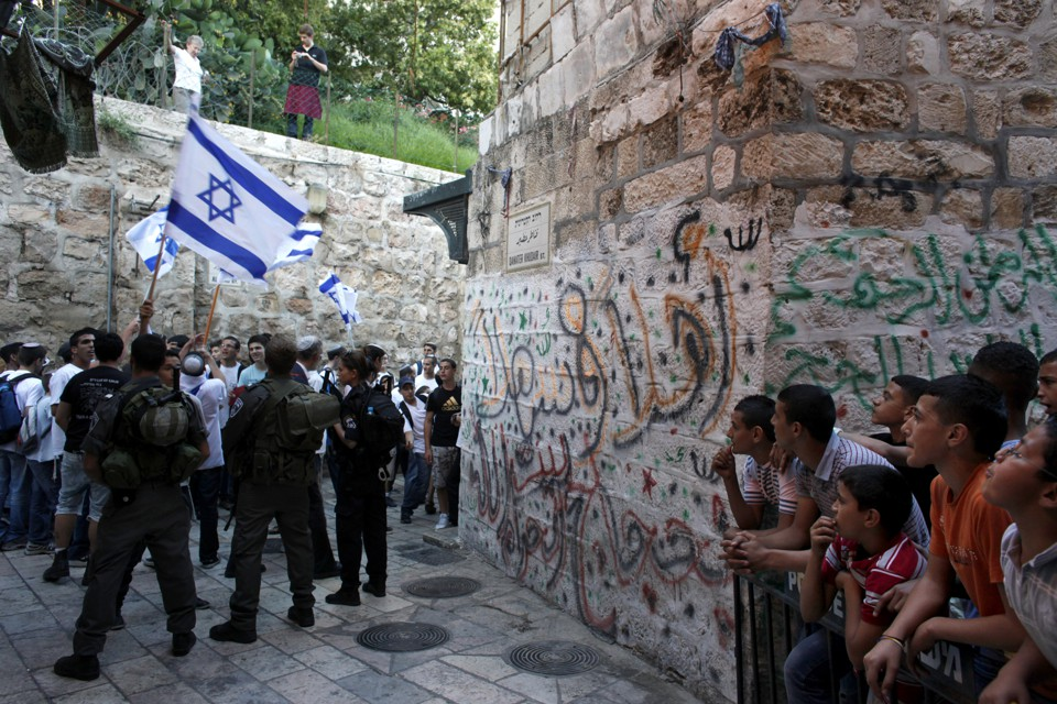 Israeli border policemen secure an alley as Israeli youth march on their way to the Western Wall.