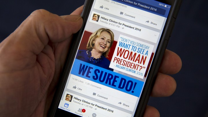 A mobile phone shows a Facebook page promoting Hillary Clinton for president in 2016.