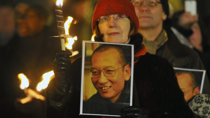 A woman holds a photograph of Xiaobo during a procession in Oslo following the 2010 Nobel Peace Prize ceremony.