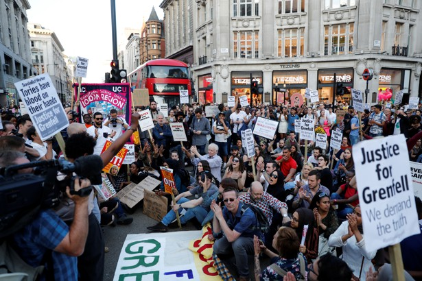 Demonstrators sit in the road during a protest in London's West End on June 16, 2017.