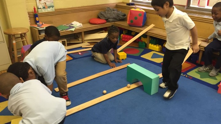 A group of pre-school students play on a blue carpet with wooden ramps and balls.