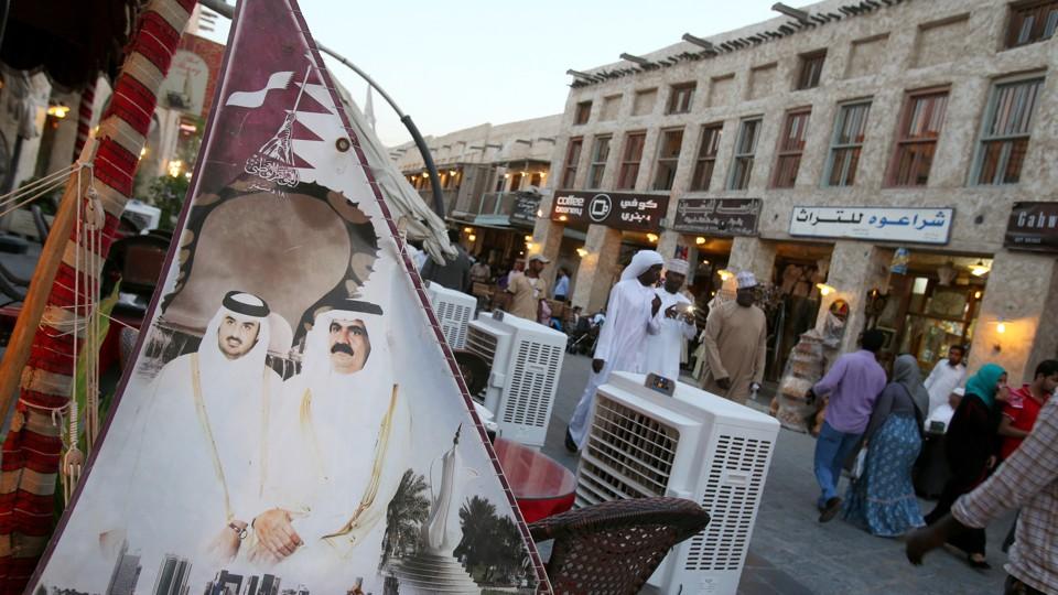 People walk past a banner bearing portraits of Qatar's former emir, Sheikh Hamad bin Khalifa al-Thani, and his son Sheikh Tamim.