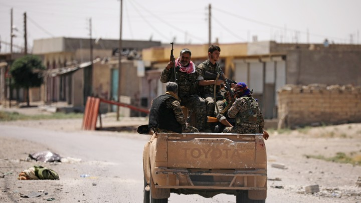 Syrian Democratic Forces (SDF) ride on a pick-up truck in Raqqa's western neighbourhood of Jazra on June 11, 2017.