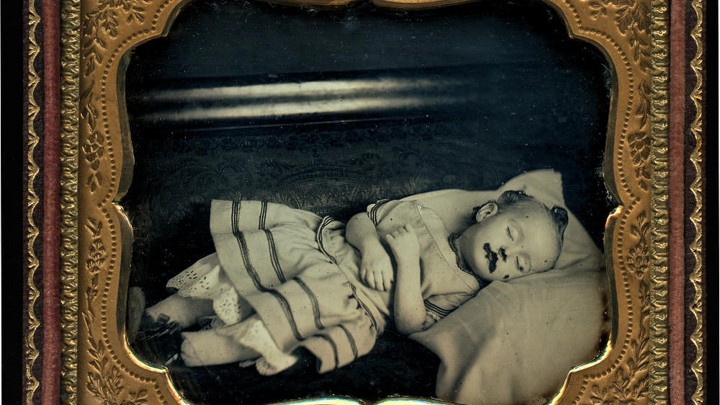 A framed black-and-white image of a deceased infant
