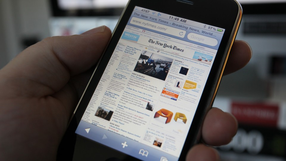 A left hand holds an iPhone with The New York Times' homepage displayed on the screen.