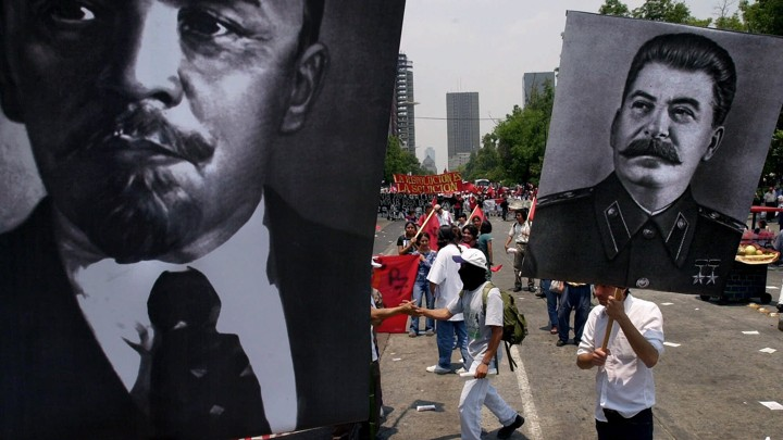 People in a demonstration carry posters with images of Lenin and Stalin.