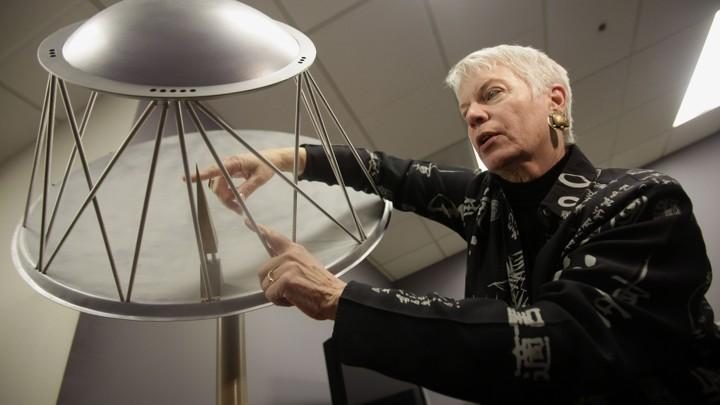SETI astronomer Jill Tarter, wearing her trademark turtle earrings, shows a model of the Allen Telescope Array in California.