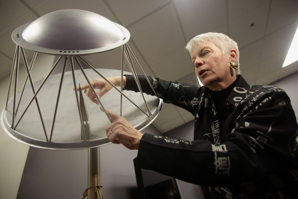 SETI astronomer Jill Tarter, wearing her trademark turtle earrings, shows a model of the Allen Telescope Array in California.