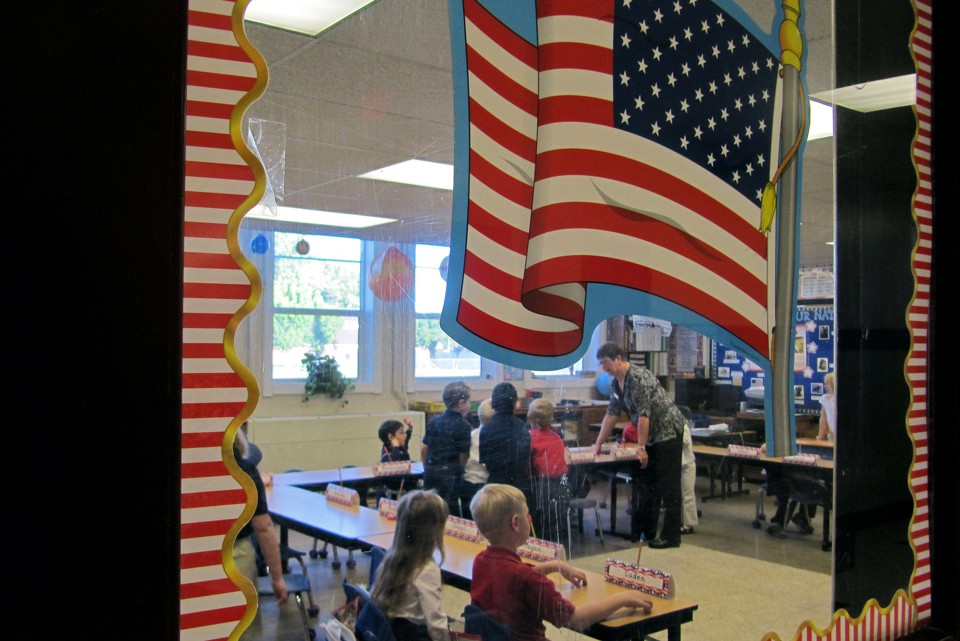 The photograph peers into an elementary school classroom through a door with an American flag sticker on it.