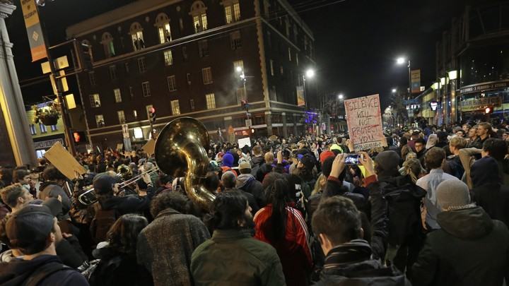A crowd of protesters, including some with signs and one with a tuba, fill the streets in Berkeley, California, protesting a speech by Milo Yiannopoulos