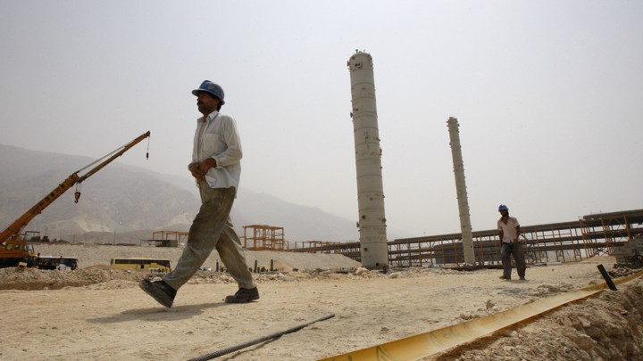 Iranian workers walk in a construction site which is part of South Pars gas field, on the northern coast of Persian Gulf, Iran.