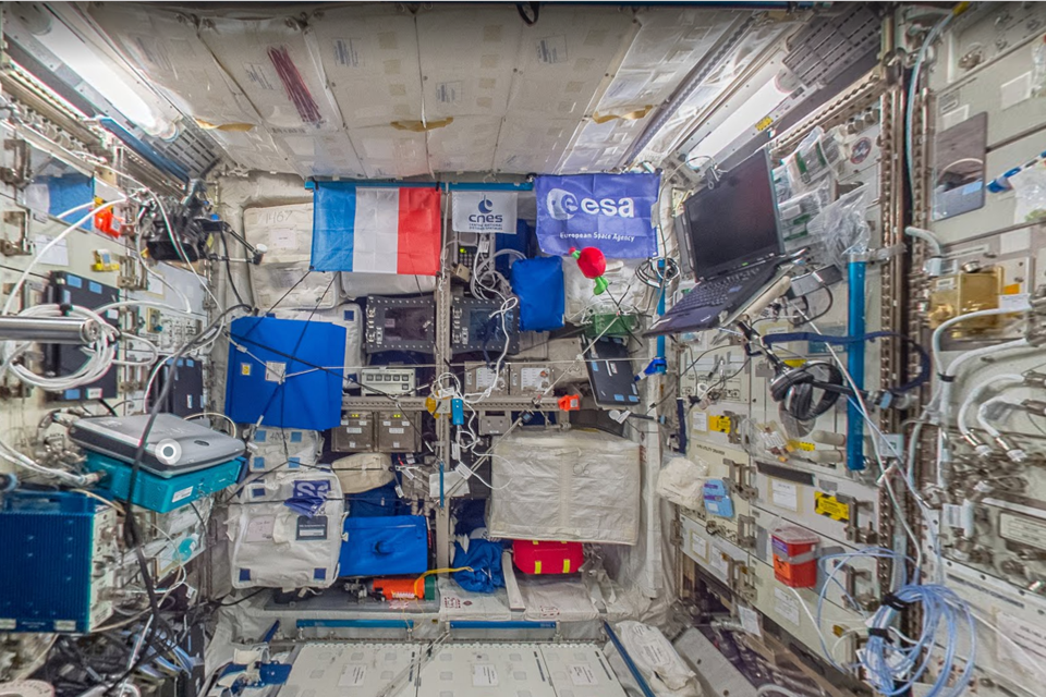 A crowded space full of electronics and a French flag