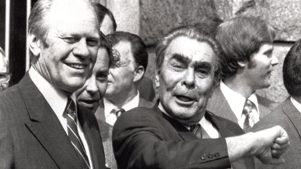 President Gerald Ford and Leonid Brezhnev smile in the foreground, while translator Victor Sukhodrev and Jan Lodal stand in the background.