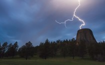 Lightning strikes near a tall, cylindrical rock formation.