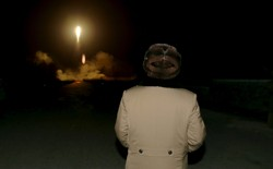 North Korean leader Kim Jong Un watches as a missile takes off.