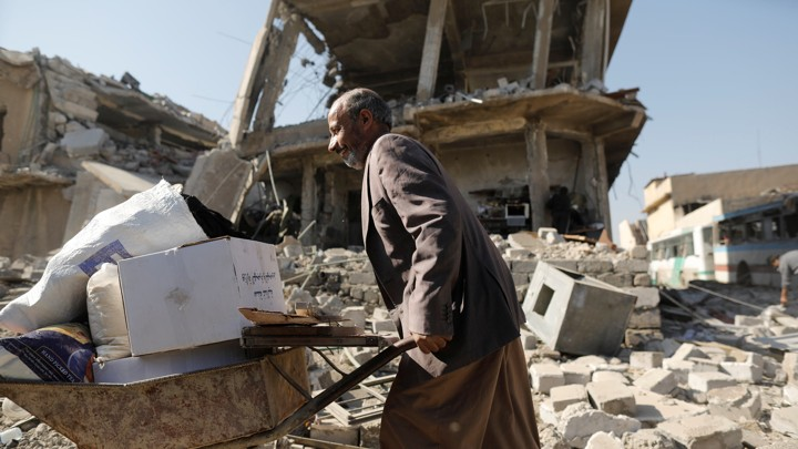 A man walks past a house destroyed during fighting between Iraqi security forces and Islamic State's fighters in Mosul, Iraq, carrying a wheelbarrow loaded with possessions.