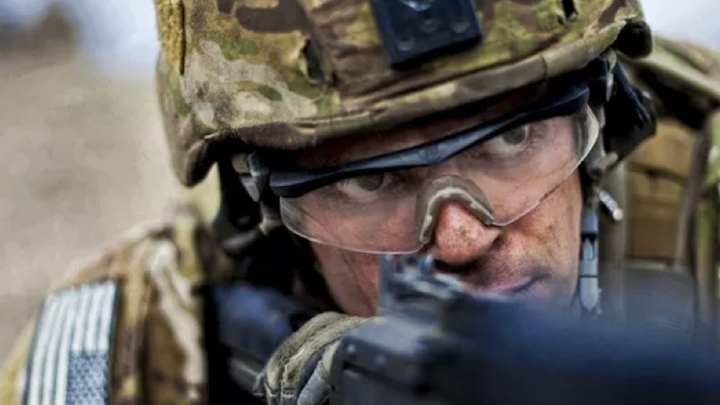 A person in camouflage clothing and helmet, wearing safety goggles, peers down the barrel of a gun.