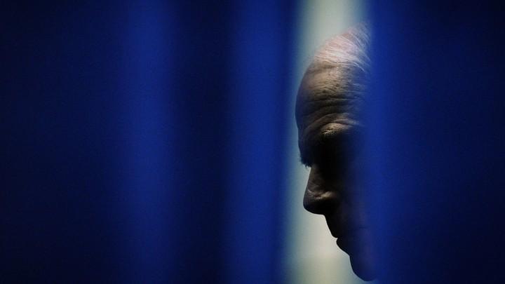 John McCain is seen through a gap in blue curtains.