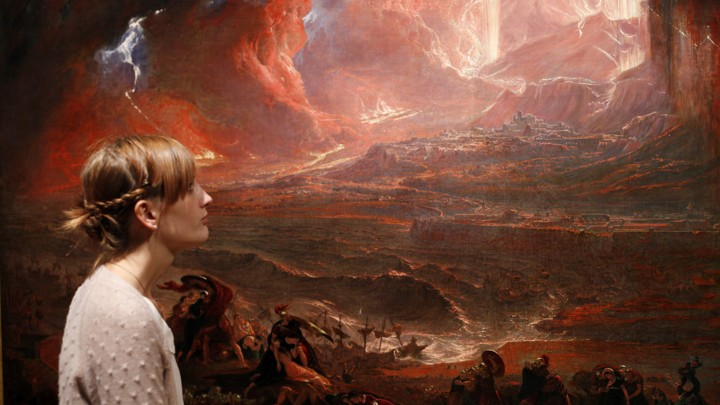 "A woman stands next to an apocalyptic painting—John Martin's ""The Destruction of Pompeii and Herculaneum""—in Tate Britain, London."