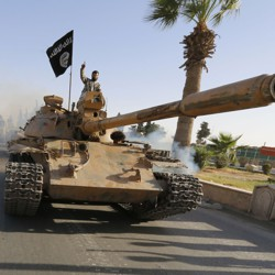 An ISIS fighter rolls down a street of Raqqa in a military tank.