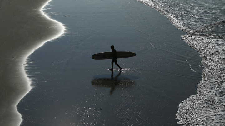 A surfer walks on the beach.