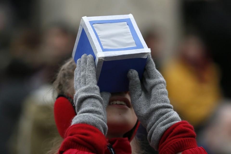 A girl looks through a viewing box.
