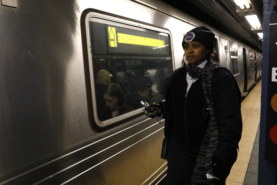 A conductor stands next to a stalled train in New York City after a power failure stopped multiple subway lines in April 2017.