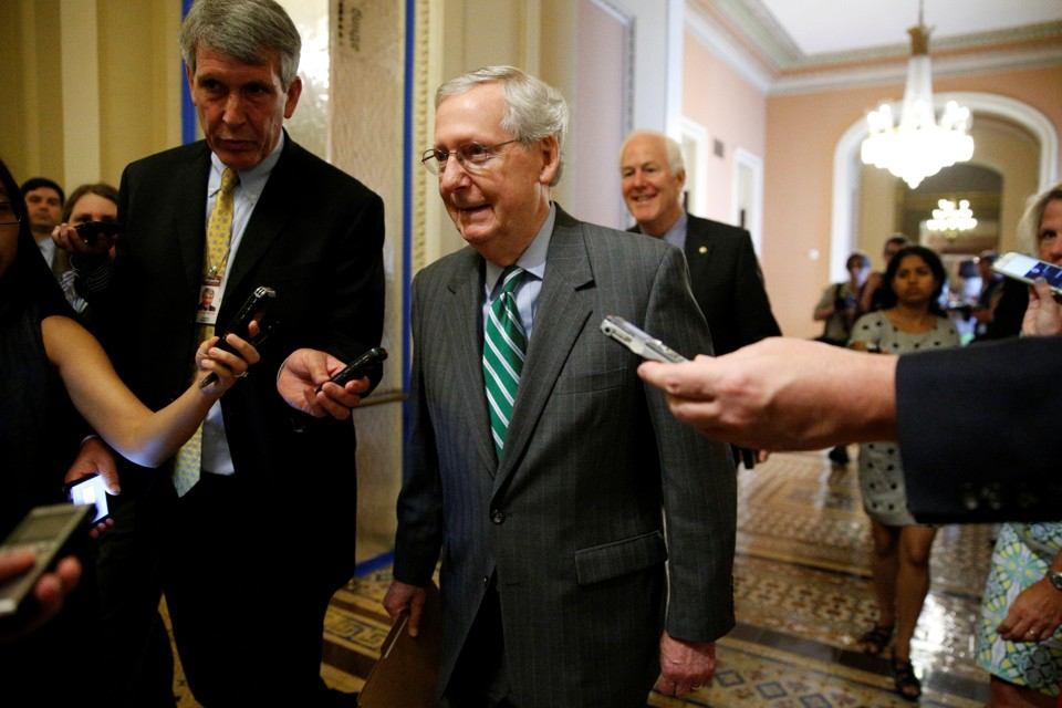 Majority Leader Mitch McConnell walks alongside reporters on Capitol Hill.