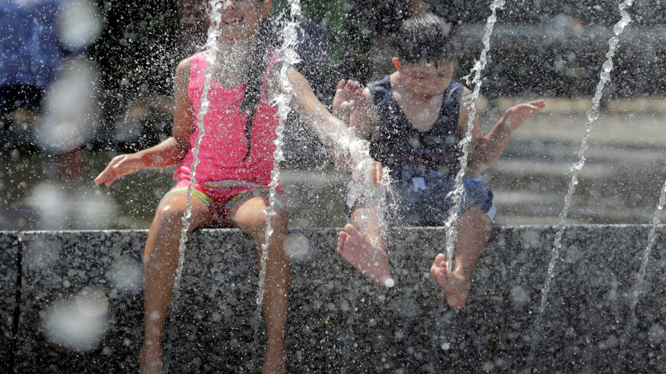 A girl in a pink tank top and a boy in a black tank top play in a fountain during a heat wave in Washington.