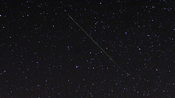 A thin diagonal line of light is shown against a starry sky.