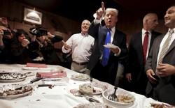 Donald Trump stands eating pie.