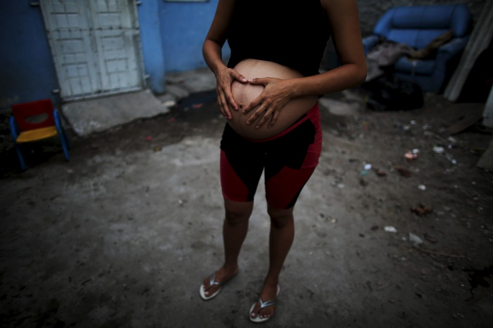 A pregnant woman stands outside her house in Recife, Brazil in February 2016.