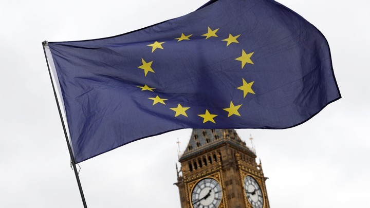 A European Union flag is waved in front of Big Ben outside the Parliament in London onMarch 28, 2017.